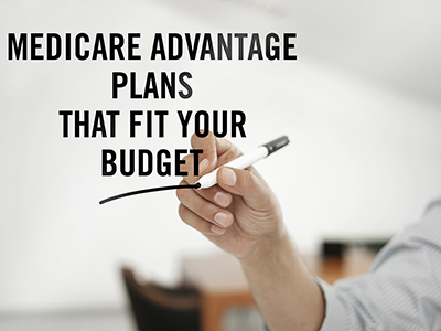 """Businessman writing """"Medicare advantage plans that for your budget"""" on a a visual board"""